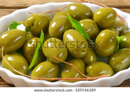 portion of green olives served on the white tray - stock photo