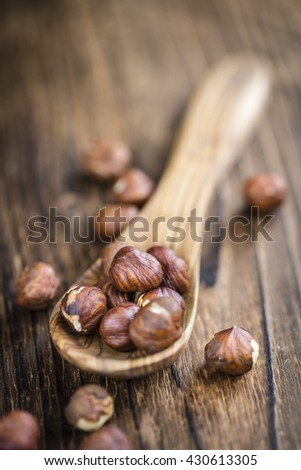 Portion of Hazelnuts (selective focus; close-up shot) on vintage background - stock photo