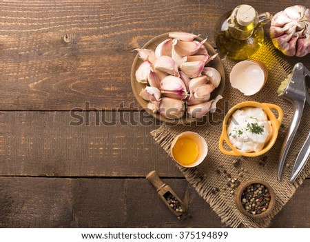 Portion of homemade Aioli dip in small bowl on wooden background - stock photo