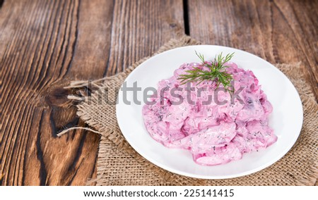 Portion of homemade Herring Salad (with beet) on wooden background - stock photo