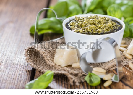 Portion of homemade Pesto Sauce with ingredients on wooden background - stock photo