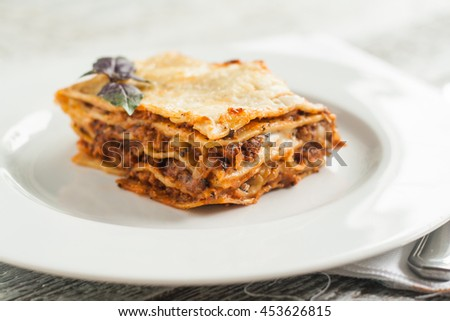 portion of lasagne bolognese on a white plate.