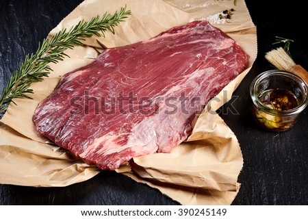 Portion of lean raw flank steak for roasting or grilling on crumpled brown paper in a rustic kitchen with a sprig of fresh rosemary and olive oil marinade - stock photo