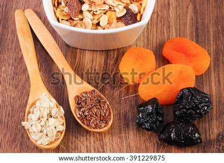 Portion of linseed and rye flakes on spoon, dried fruits and muesli, concept of healthy nutrition and increase metabolism, ingredients with dietary fiber - stock photo