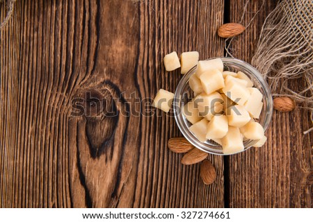 Portion of Marzipan (close-up shot) on wooden background - stock photo