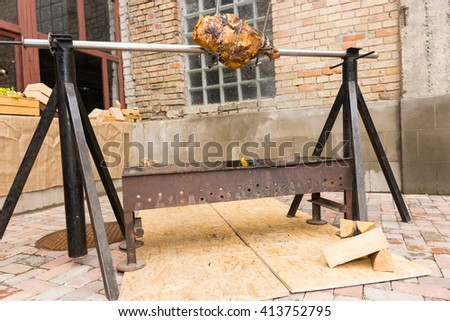 Portion of meat roasting on a rotating spit or rotisserie over an open fire in a courtyard at a catered event or party - stock photo
