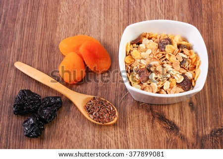 Portion of muesli in glass bowl, linseed on spoon and dried fruits, concept of healthy nutrition and increase metabolism, ingredients with dietary fiber - stock photo