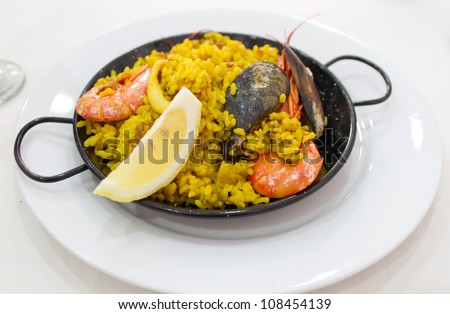 Portion of paella served in traditional metal plate - stock photo