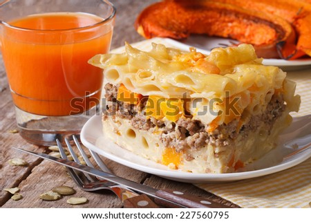 Portion of pasta baked with meat, cheese and pumpkin on a plate and vegetable juice  - stock photo