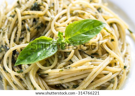Portion of pasta with pesto sauce and basil leaf