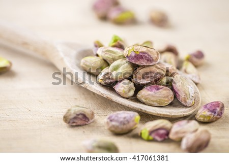 Portion of peeled Pistachios (close-up shot; selective focus) on vintage background