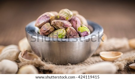Portion of peeled Pistachios (close-up shot; selective focus) on vintage background - stock photo