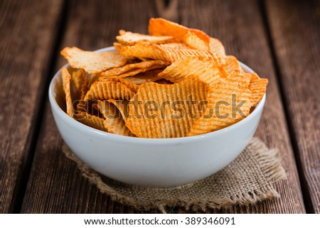 Portion of Potato Chips (rippled, selective focus) on wooden background - stock photo