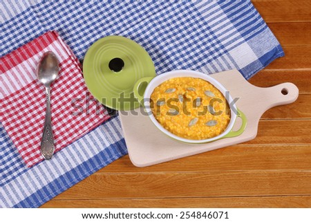 Portion of pumpkin porridge on a wooden table. Useful dietary breakfast. Pumpkin puree with millet porridge. Diet food. Healthy food. In the kitchen. - stock photo