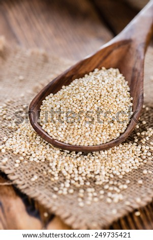 Portion of Quinoa (close-up shot) on a wooden spoon) - stock photo