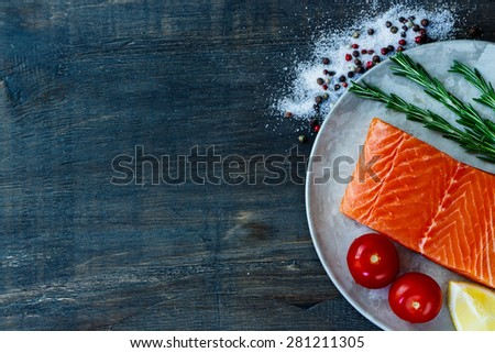 Portion of raw salmon on old metal plate with rosemary and aromatic spices. Seafood on dark wooden background with space for text. Vegetarian food, health or cooking concept. - stock photo