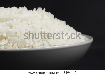 Portion of rice in a white bowl closeup photo against dark background