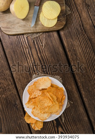 Portion of rippled Potato Chips (selective focus) on an old wooden table - stock photo