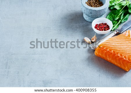 Portion of salmon fillet with fresh ingredients for tasty cooking on grey background, border, selective focus. Healthy or diet food concept. - stock photo