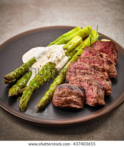 Portion Of Sliced Beef Steak And Asparagus On Dark Plate