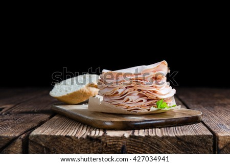 Portion of sliced Chicken Breast Fillet (close-up shot) on an old wooden table - stock photo