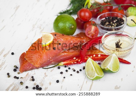 Portion of smoked salmon fillet with vegetables, aromatic spices and herbs on a wooden background - stock photo