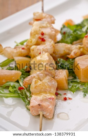 portion of spicy salmon on rocked salad