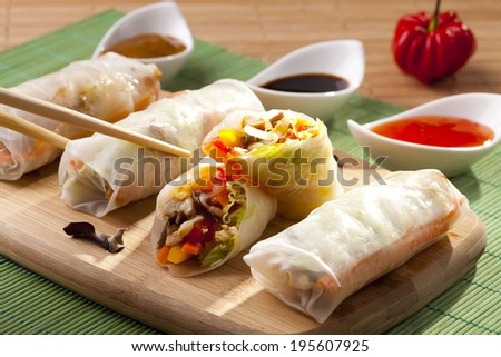 Portion of spring rolls on a bamboo board with dipping sauce - stock photo