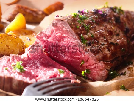 Portion of succulent rare roast beef carved for dinner with a close up view of the texture of the healthy lean red meat - stock photo