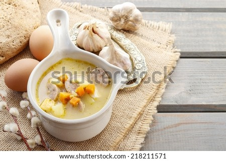 Portion of the sour rye soup made of soured rye flour and meat (usually boiled pork sausage or pieces of smoked sausage, bacon or ham) - stock photo