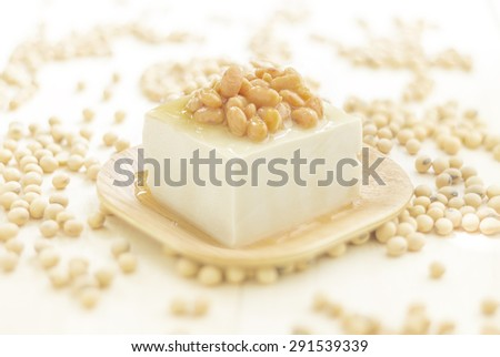 Portion of Tofu ingredients on random soy beans and wooden background, extreme shallow DOF - stock photo