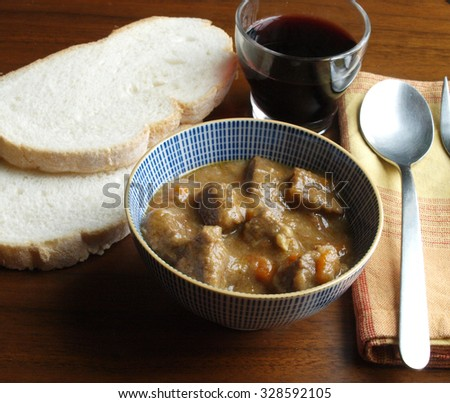 Portion of traditional beef  stew with carrots in a bowl with bread and wine      - stock photo