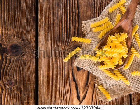 Portion of uncooked Pasta (Fussili) on rustic wooden background - stock photo
