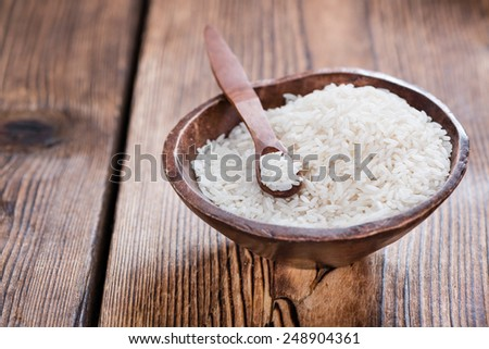 Portion of uncooked Rice on rustic wooden background - stock photo