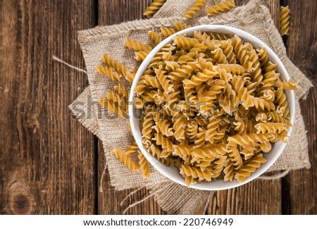 Portion of uncooked Wholemeal Fussili on wooden background - stock photo