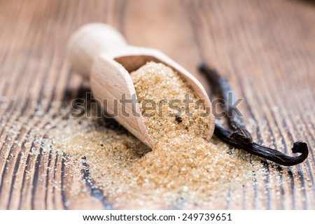 Portion of Vanilla Sugar (Brown) on rustic background - stock photo
