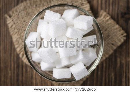 Portion of white Sugar (selective focus) in a bowl (on vintage wooden background) - stock photo