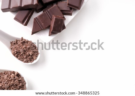 Portions and chocolate chips on a white porcelain container on a white wooden table isolated. Horizontal composition. Top view - stock photo