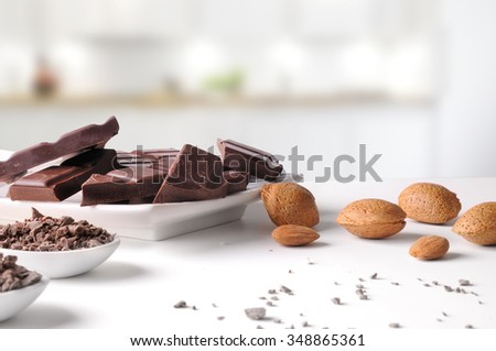 Portions and chocolate chips with almonds on a white porcelain container on a white table in kitchen. Horizontal composition. Front view - stock photo