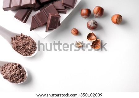 Portions and chocolate chips with hazelnuts on a white porcelain container on a white wooden table isolated. Horizontal composition. Top view - stock photo
