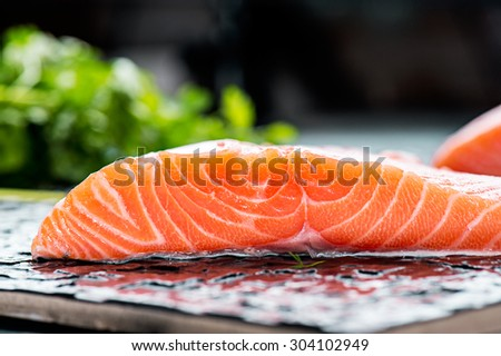 portions of fresh gourmet uncooked salmon fillet on black background  - stock photo