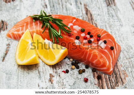 portions of fresh salmon fillet with aromatic herbs, spices and lemons - stock photo