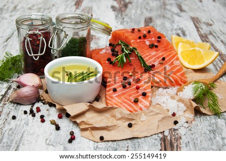 portions of fresh salmon fillet with aromatic herbs, spices and vegetables - stock photo