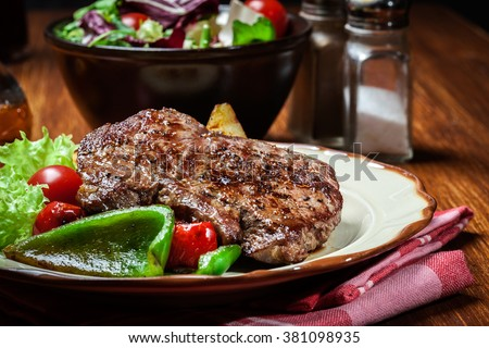 Portions of grilled beef steak served with grilled potatoes and paprika - stock photo