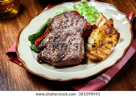 Portions of grilled beef steak served with grilled potatoes and paprika