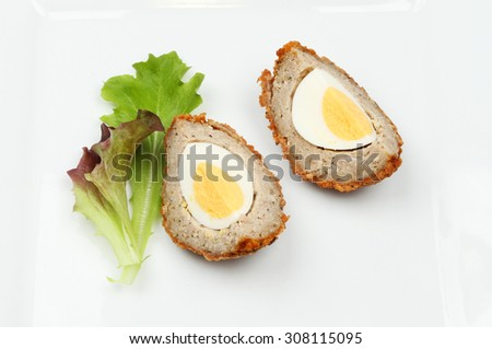 Portions of scotch egg on a plate with lettuce leaves
