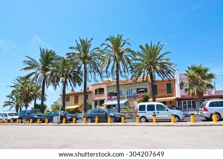 PORTIXOL, MALLORCA, BALEARIC ISLANDS, SPAIN - JULY 26, 2015: Village street scene with palm trees and cars on July 26, 2015 in Portixol, Mallorca, Balearic islands, Spain in July.