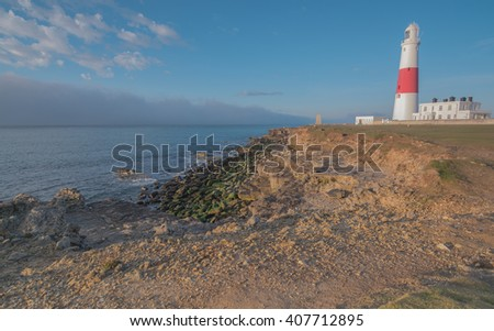 Portland Bill Lighthouse preparing to sound his fog horn, as a huge fog bank rolls in from the sea. Taken at the Isle of Portland, Dorset, UK. - stock photo