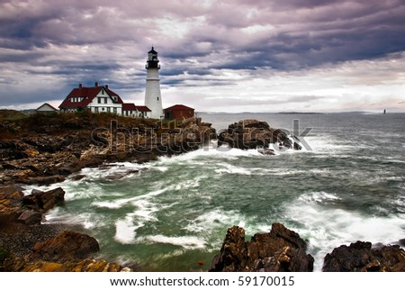 Portland Head Lighthouse sits on the edge of the Atlantic Ocean while the waves crash on the rocky coast - stock photo