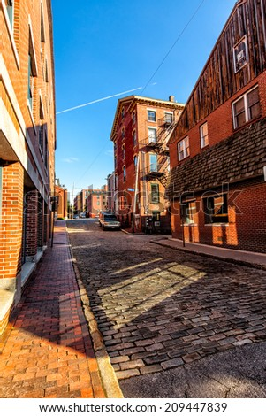 Portland, Maine cobblestone street and old red brick buildings in the waterfront district. Colorful image on a sunny day with bright blue sky throwing reflections from windows onto the street. - stock photo